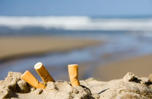 Cigarette butts sticking out of the sand on a beach
